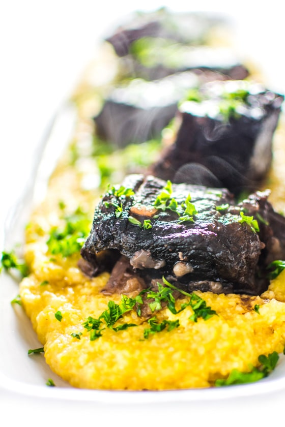 This super EASY and delicious recipe for braised short ribs calls on red wine, creamy polenta and winter root vegetables for an elegant, comforting meal. | rootandrevel.com
