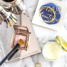 A variety of makeup and skincare products and jewelry on a counter.