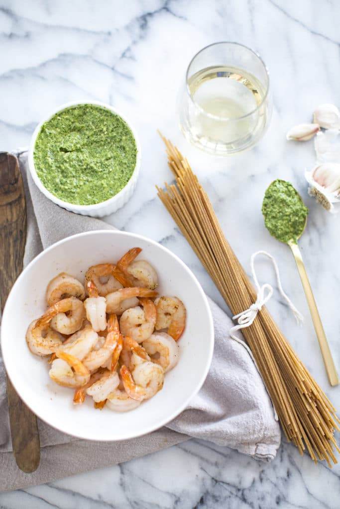 Steamed shrimp in a white bowl on a counter with uncooked pasta, pesto, and a glass of wine.