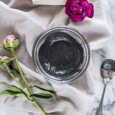 A homemade Activated Charcoal and Clay Mask in a dish on a table with flowers.