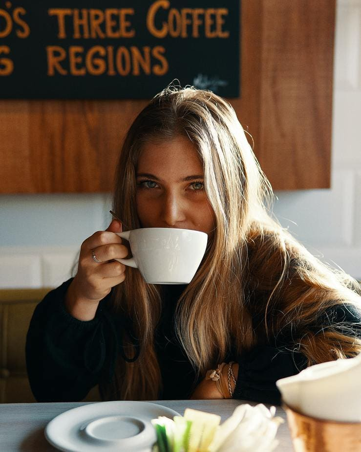 woman drinking coffee at a desk.