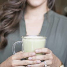 A woman holding a matcha green tea latte in a clear mug.