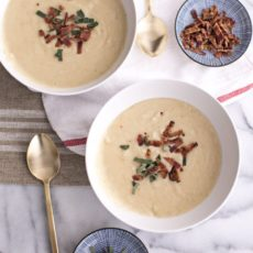 Cauliflower soup in white bowls topped with bacon on a table setting