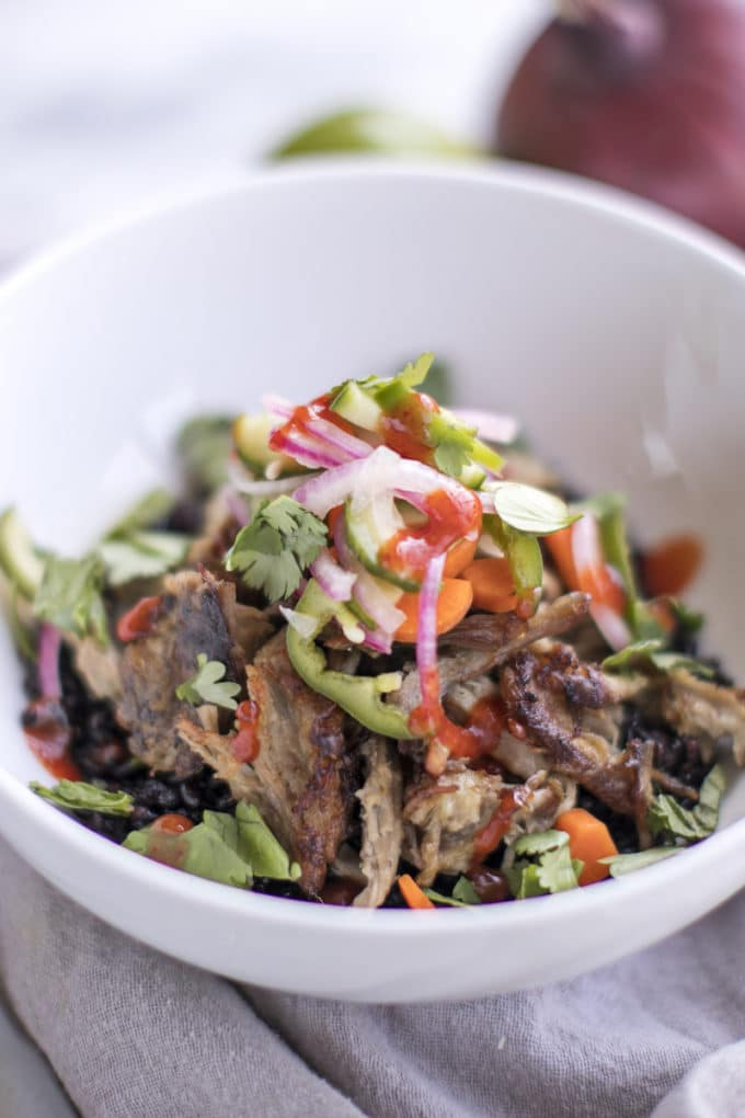 This recipe for Slow Cooker Pulled Pork Banh Mi Bowls puts a healthy twist on the classic Vietnamese sandwich. Made in the crockpot with pork shoulder (or pork butt) with a delicious Asian marinade, this tender pulled pork is topped with fresh pickled veggies and served over heirloom rice.