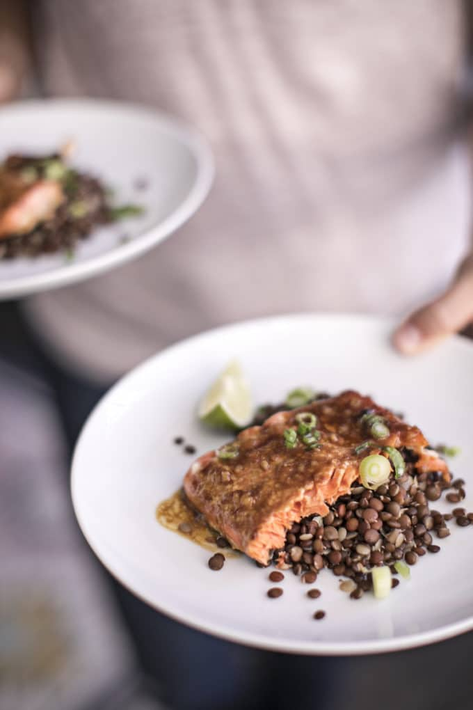 Miso glazed salmon over lentils on a white plate being carried.