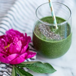 green smoothie in a glass with a straw next to a pink flower on a countertop.