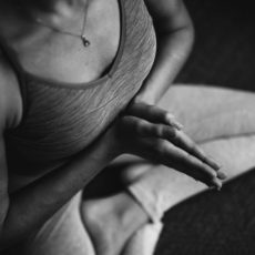 Woman laying down on a pink yoga mat in corpse pose