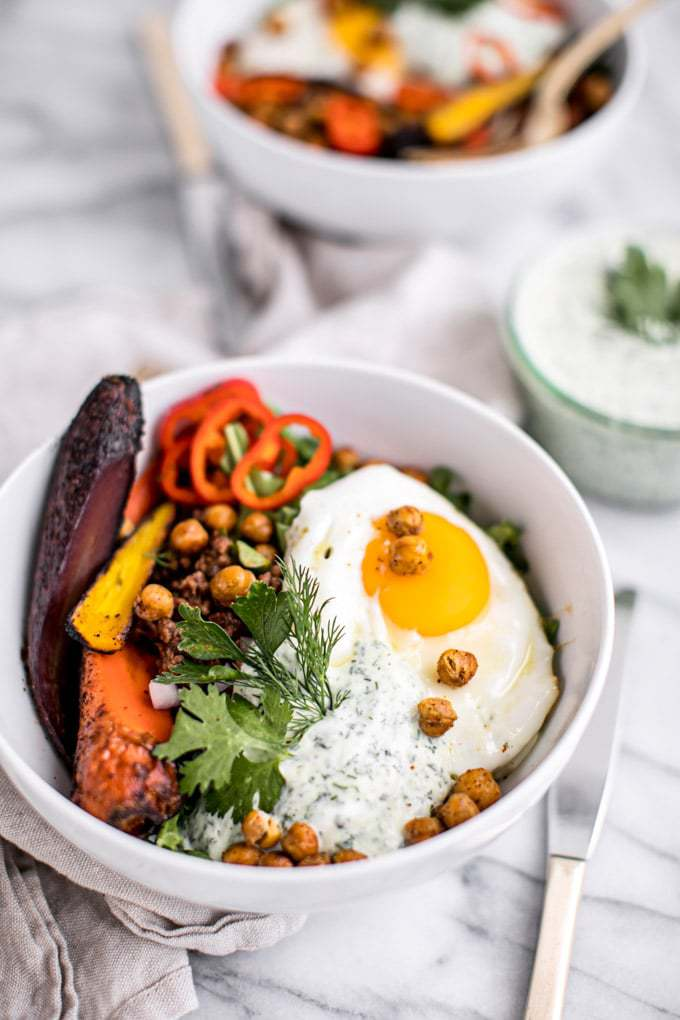 A white bowl with lamb, an over easy eggs, peppers, chickpeas, and green herbs.