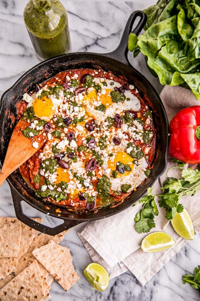 Shakshuka (Eggs in Tomato Sauce) is an easy and healthy Isreali-inspired breakfast--it's a delicious vegetarian and Paleo-friendly recipe spiked with green Swiss Chard Pesto and flavorful spices, like harissa, topped with feta, olives, and capers. The perfect breakfast for two (or one, with leftovers!)