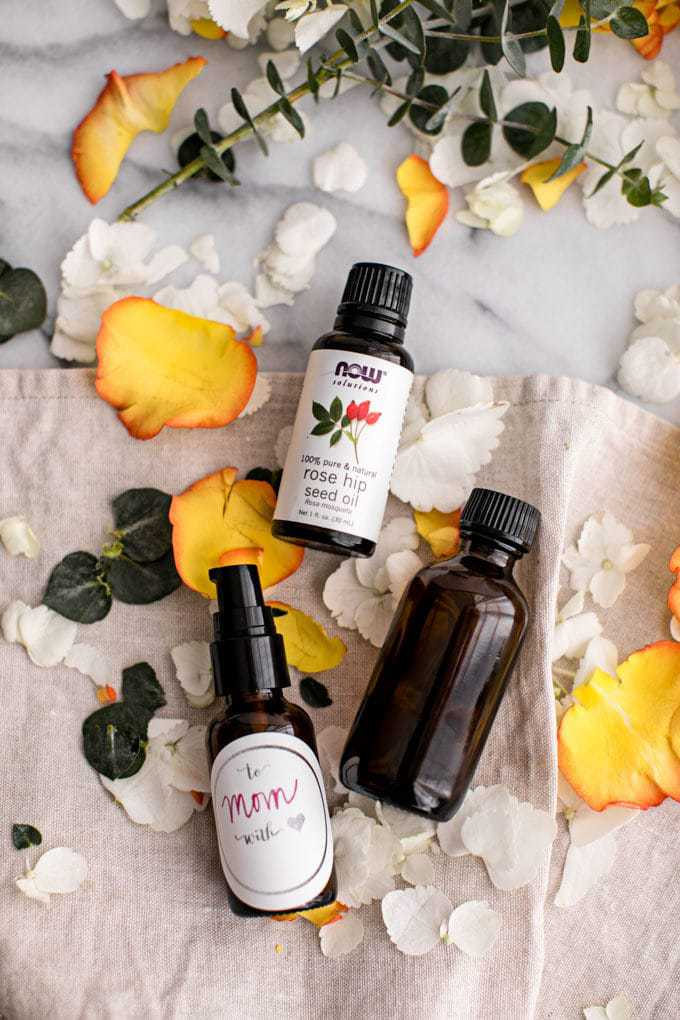This Custom DIY Homemade Face Oil Recipe is made with rose hip oil and on display with flower petals.