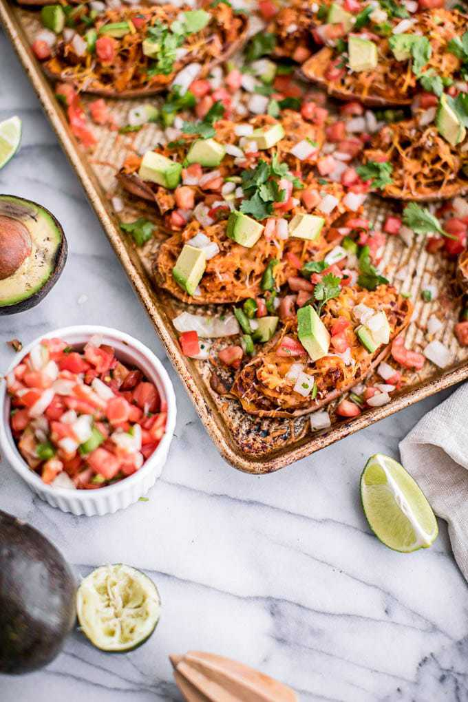 This Twice Baked Stuffed Sweet Potato Skins Recipe is loaded with savory chipotle beans and guacamole for an easy, healthy and tasty appetizer perfect for Cinco de Mayo or your next party. This Mexican-inspired recipe is vegetarian, gluten-free and DELICIOUS!