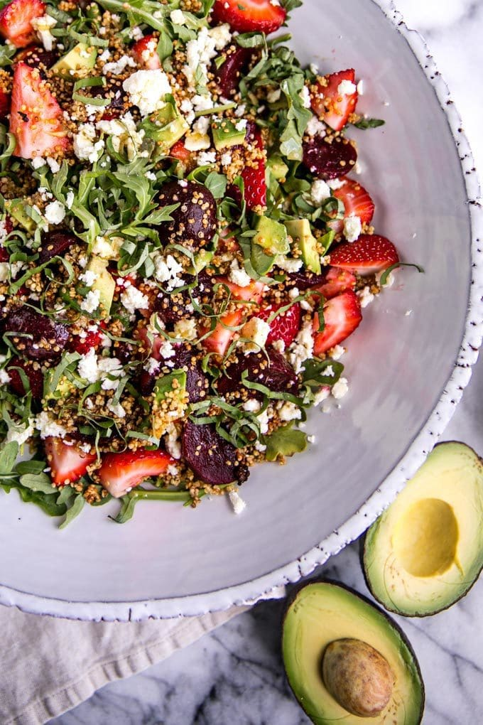 Just in time for summer BBQs, this Strawberry + Pickled Beet Salad with White Balsamic Dressing is an easy, healthy side dish. Garnished with feta, avocado, crispy quinoa and a tangy vinaigrette, this gluten-free and vegetarian arugula salad is a summertime classic!