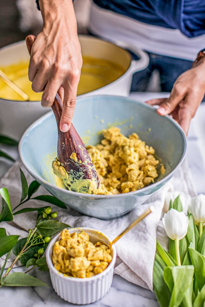 Creamy vegan mac and cheese being stirred in a light blue bowl and served into small ramekins.