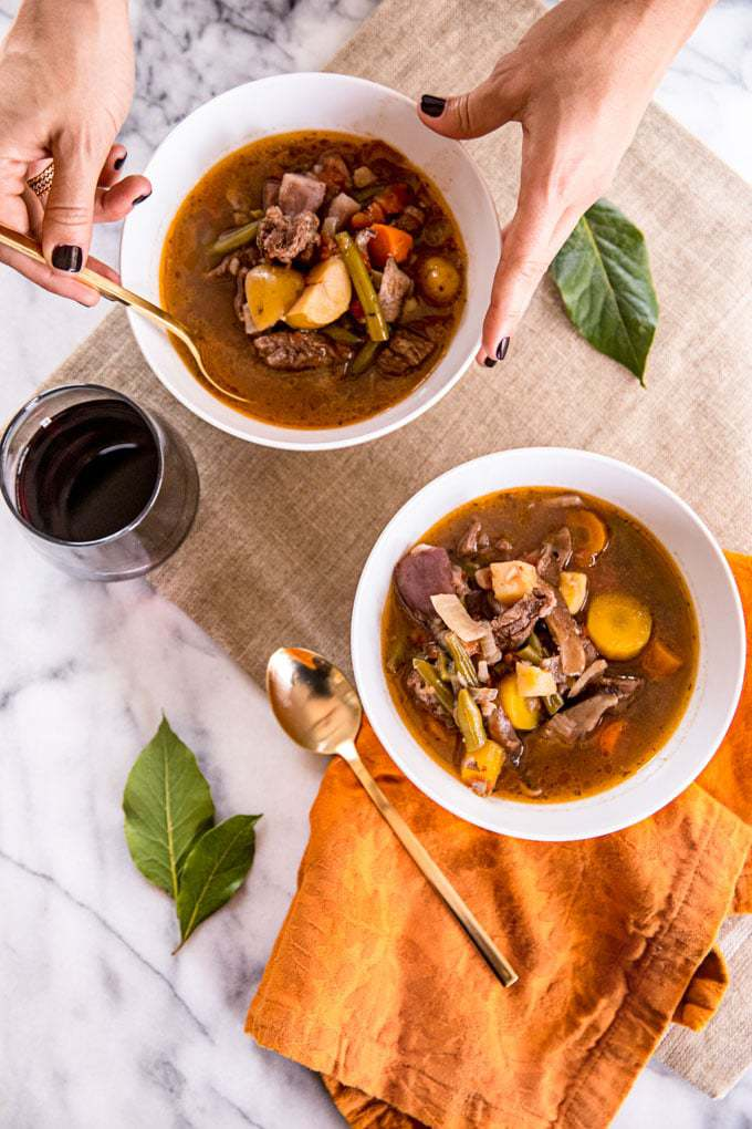 Two bowls of low carb beef stew on a table with a placemat, dish towel, and gold spoons, and two hands with one touching a spoon.