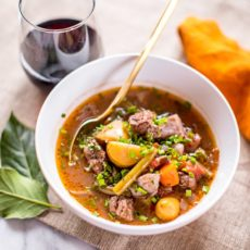 Keto Beef Stew with meat and veggies in a white bowl with a gold spoon and a glass of wine.