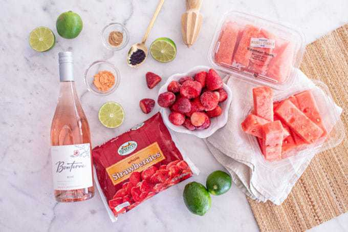Ingredients for Superfood Frosé (aka Wine Slushies) - wine, watermelon, strawberries, lime, and superfood powders.