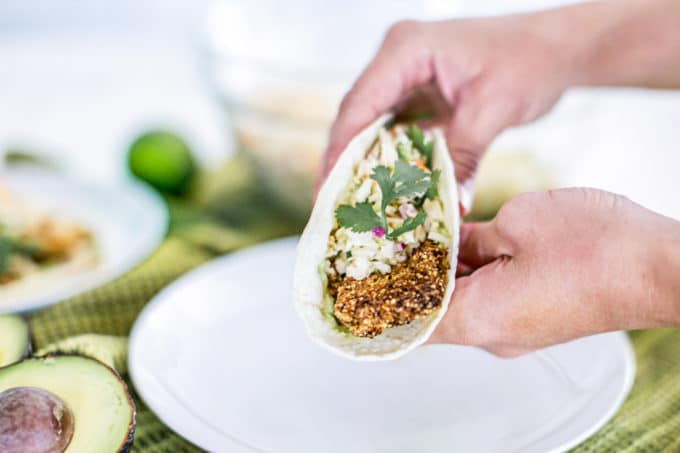 Crispy, crunchy and savory baja fish tacos that are also healthy and gluten free? Yes! It IS possible to make lightened up, real food fried tacos that make for a perfect summer meal. In this recipe, we'll show you how it's done, complete easy-to-make with Avocado Crema sauce + Chipotle Coleslaw.
