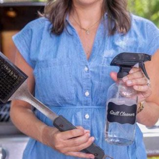 A woman in a blue dress is holding a grill brush and spray bottle labeled with the words Grill Cleaner.