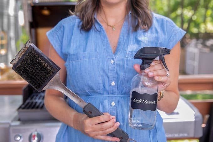 A woman holding a grill brush and a grill cleaner bottle.