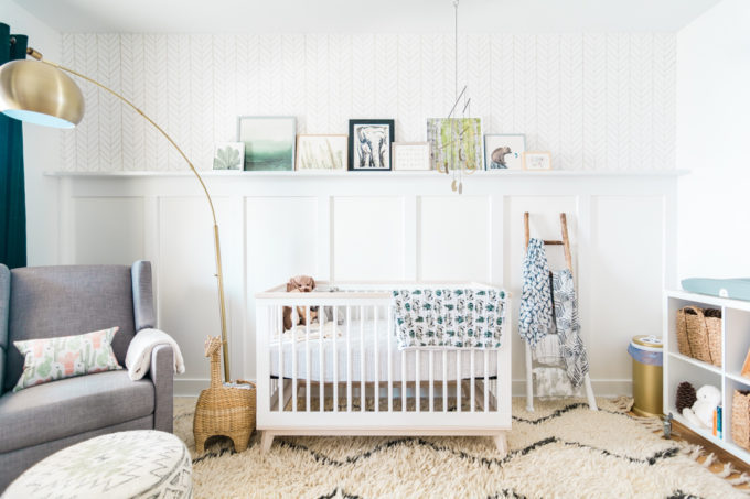 A baby nursery with a crib, glider, shelves, and decorations.