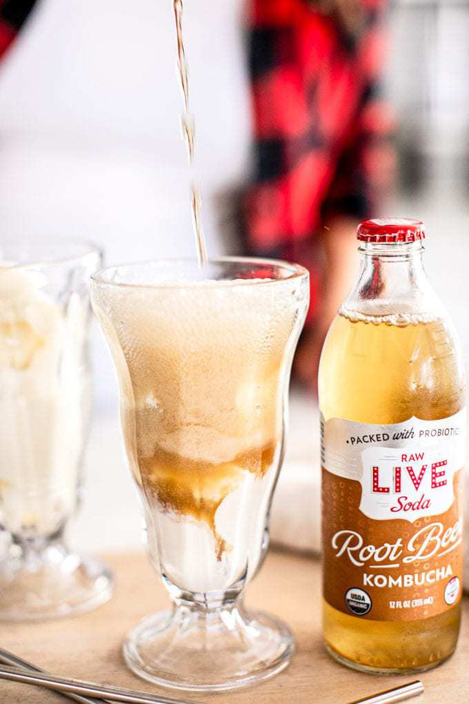 Root beer kombucha being poured into glass ice cream dishes with vanilla ice cream on the bottom.