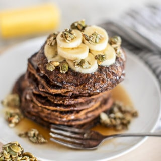 A stack of pumpkin pancakes with banana and syrup.