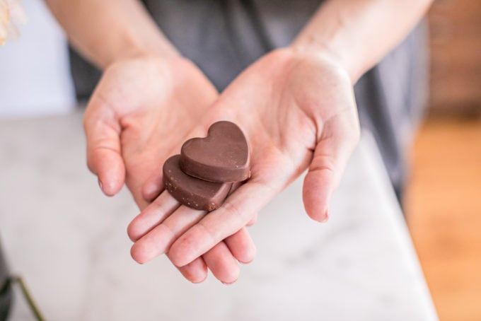 Two chocolate hearts in the palm of hands.