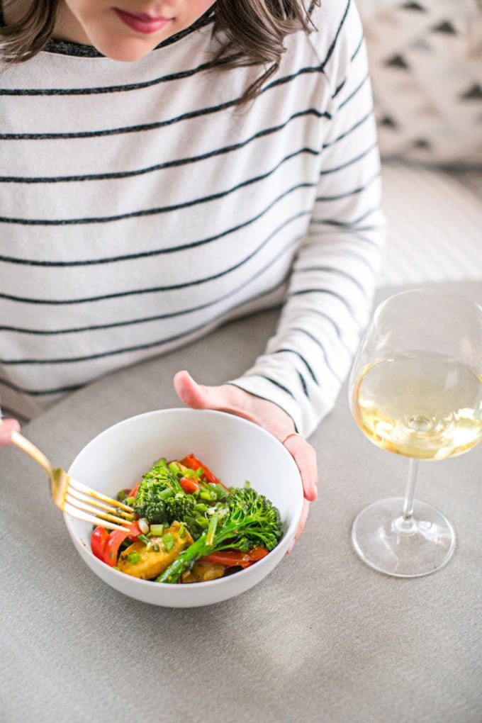 A woman sitting at a table holding a bowl of vegetables with a glass of white wine.