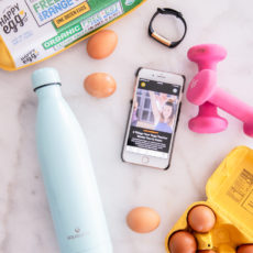 Cartons of organic eggs with an iphone, weights, watch and waterbottle all on a counter.