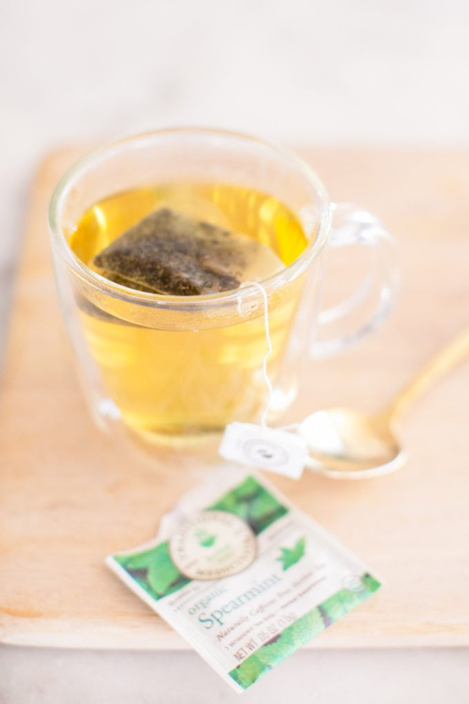 A glass mug filled with Spearmint tea with the tea bag and gold spoon on the side.