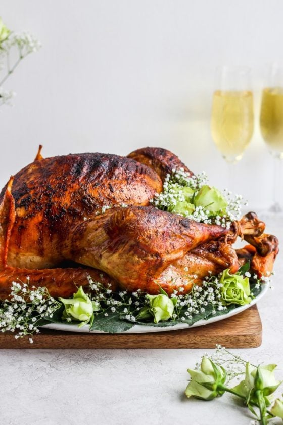 A roasted turkey on a platter garnished with flowers and champagne flutes in the background.