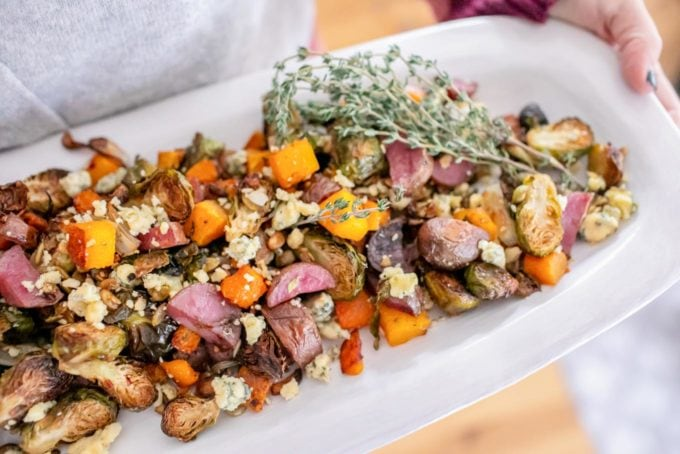 Roasted root vegetables topped with blue cheese and pumpkin seeds on a big white platter.