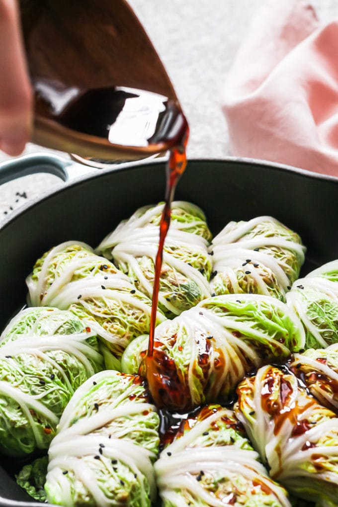 Cabbage rolls in a pan with sauce being drizzled on top.