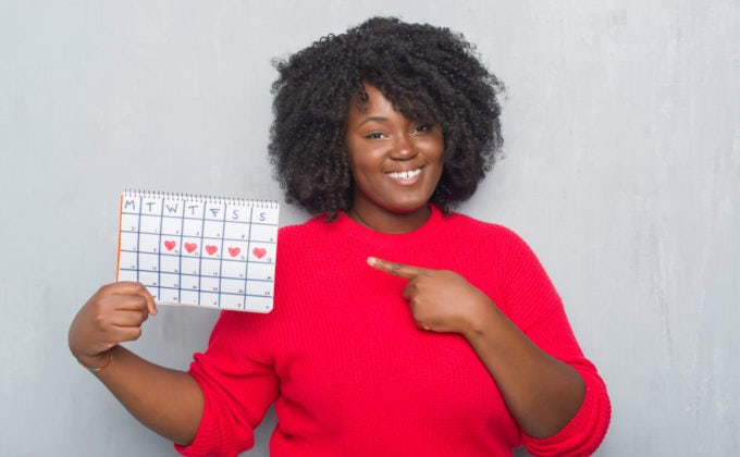 Black woman in a red dress holding up a calendar.