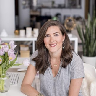 Kate Kordsmeier, woman sitting on a colorful rug at a coffee table with a notebook.