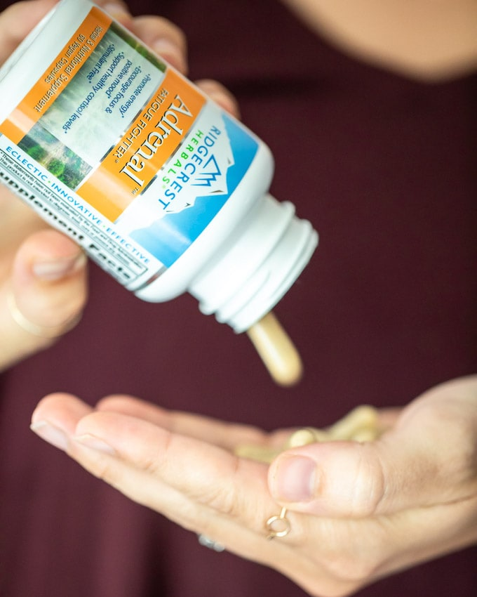 A bottle of Adrenal Fatigue supplement being poured into a hand