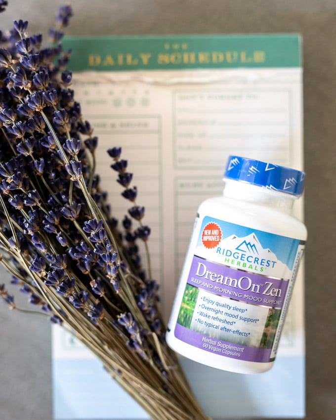 A bottle of Ridgecrest Herbals' DreamOn Zen next to lavender and on top of a schedule