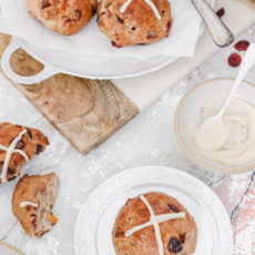 Hot Cross Buns on white plates on a table.