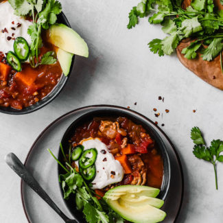 Slow cooker turkey chili in a grey bowl on a grey plate with toppings