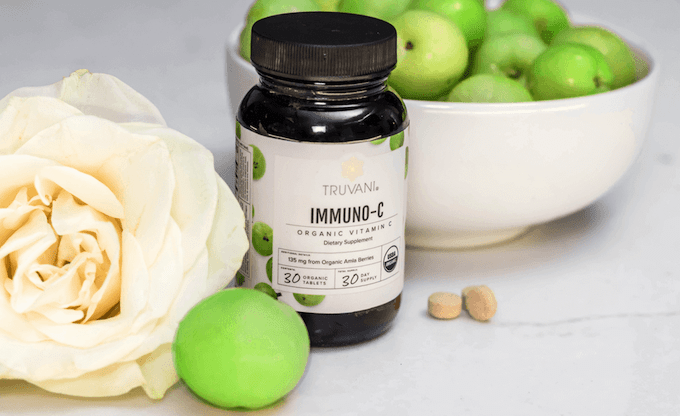 Truvani's Immuno-C organic vitamin C supplement on a table with green apples.