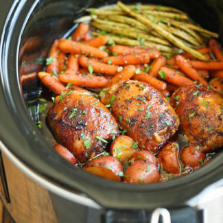 Chicken thighs, carrots and asparagus in a slow cooker.