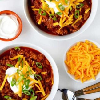 Chicken chili in white bowls with spoons and cheese on the side.